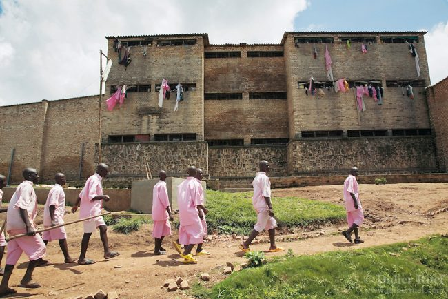 Rwanda. Southern province. District of Muhanga. Central jail of Gitarama. A group of black teenager boys, wearing the pink prisoner's clothes, walk outside of the prison. They are returning to the minors block. Minors in detention. Detention pending trial and after trial, when sentenced to prison.
